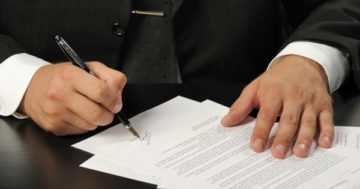 Человек подписывает договор дарения
